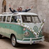 zwei Männer feiern ihre Verpartnerung im Hochzeitsbus