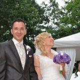 Glückliches Brautpaar nimmt nach der Trauung Glückwünsche entgegen
