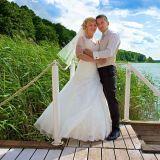 Der Bräutigam hält seine Braut am Bootssteg liebevoll im Arm